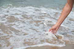 Bottle-sea. Hand holding a bottle with a letter inserted inside by the sea Royalty Free Stock Photo