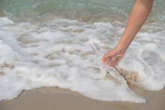 Bottle-sea. Hand holding a bottle with a letter inserted inside by the sea Stock Photos