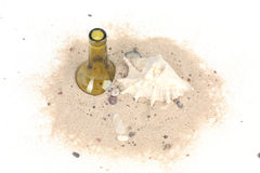 Bottle and seashell in beach sand on white background Royalty Free Stock Images