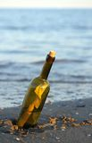 Bottle with a secret message on the shore of sandy beach Royalty Free Stock Photos
