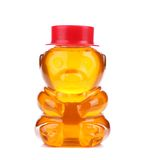 Bottle shaped like a bear and filled with honey. Royalty Free Stock Images