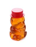 Bottle shaped like a bear and filled with honey. Royalty Free Stock Photos