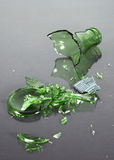 Bottle shattered. A green glass bottle shattered on a black reflective background Stock Photo