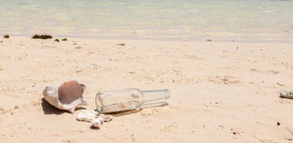 Bottle and shell on Caribbean beach Stock Photos