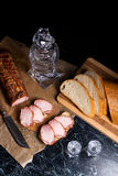 Bottle and shot glass with vodka with slices of smoked meat on b. Bottle and shot glasses with vodka. Small snack of bread and meat near the shot glass. Slices Stock Photography