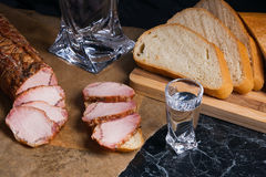 Bottle and shot glass with vodka with slices of smoked meat on b. Bottle and shot glasses with vodka. Small snack of bread and meat near the shot glass. Slices Royalty Free Stock Images