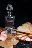 Bottle and shot glass with vodka with slices of smoked meat on b Stock Photography
