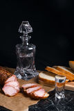 Bottle and shot glass with vodka with slices of smoked meat on b. Bottle and shot glasses with vodka. Small snack of bread and meat near the shot glass. Slices Royalty Free Stock Photography