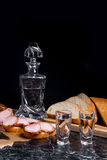 Bottle and shot glass with vodka with slices of smoked meat on b. Bottle and shot glasses with vodka. Small snack of bread and meat near the shot glass. Slices Stock Images
