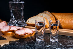 Bottle and shot glass with vodka with slices of smoked meat on b. Bottle and shot glasses with vodka. Small snack of bread and meat near the shot glass. Slices Royalty Free Stock Photo