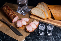 Bottle and shot glass with vodka with slices of smoked meat on b. Bottle and shot glasses with vodka. Small snack of bread and meat near the shot glass. Slices Stock Image