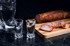 Bottle and shot glasses with vodka with slices of smoked meat on. Bottle and shot glasses with vodka. Slices of smoked meat or ham on wooden cutting board Stock Image