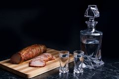 Bottle and shot glasses with vodka with slices of smoked meat on. Bottle and shot glasses with vodka. Slices of smoked meat or ham on wooden cutting board Royalty Free Stock Image