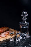Bottle and shot glasses with vodka with slices of smoked meat on. Bottle and shot glasses with vodka. Slices of smoked meat or ham on wooden cutting board Royalty Free Stock Photos
