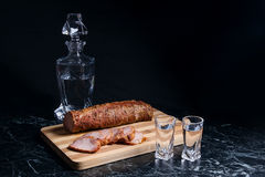 Bottle and shot glasses with vodka with slices of smoked meat on. Bottle and shot glasses with vodka. Slices of smoked meat or ham on wooden cutting board Royalty Free Stock Photography