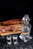 Bottle and shot glasses with vodka with slices of smoked meat on. Bottle and shot glasses with vodka. Slices of smoked meat or ham on wooden cutting board Royalty Free Stock Photo