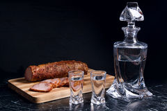 Bottle and shot glasses with vodka with slices of smoked meat on. Bottle and shot glasses with vodka. Slices of smoked meat or ham on wooden cutting board Stock Photography