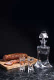 Bottle and shot glasses with vodka with slices of smoked meat on. Bottle and shot glasses with vodka. Slices of smoked meat or ham on wooden cutting board Stock Images