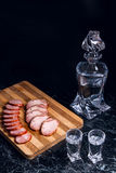 Bottle and shot glasses with vodka, slices of smoked meat and sm. Bottle and shot glasses with vodka. Slices of smoked meat or ham and smoked sausage on wooden Royalty Free Stock Photography