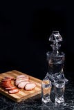 Bottle and shot glasses with vodka, slices of smoked meat and sm. Bottle and shot glasses with vodka. Slices of smoked meat or ham and smoked sausage on wooden Stock Photography