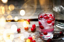 Bottle and Shot of Vodka with Raspberry on old wooden background with bokeh. A Bottle and Shot of Vodka with Raspberry on old wooden background with gold bokeh Royalty Free Stock Photos