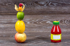Bottle smoothie with fresh apple, lemon, lime, physalis, raspberries. On wooden table Stock Photos