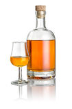 Bottle and snifter filled with amber liquid stock image