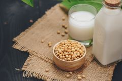 Bottle of soy milk and soybean on wooden table Stock Photography