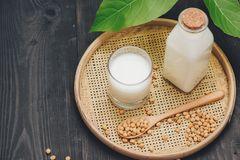 Bottle of soy milk and soybean on wooden table.  stock photos