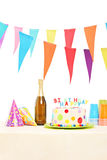 Bottle of sparkling wine, plastic glasses, party hats and birthd Stock Photo