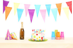 Bottle of sparkling wine, plastic glasses, party hats and birthd Stock Photography