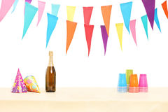 Bottle of sparkling wine, plastic glasses and party hats Stock Photo
