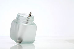 Bottle and spoon. A tea spoon in a empty bottle Royalty Free Stock Photography