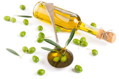 Bottle and spoon of olive oil, green olives. Spoon of olive oil, small bottle with olive oil, decorated with a small twig with green olives fruit,  on white Royalty Free Stock Photography