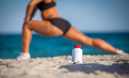 Bottle of sports food on sand Royalty Free Stock Photography