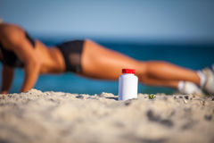 Bottle of sports food on sand Royalty Free Stock Photos