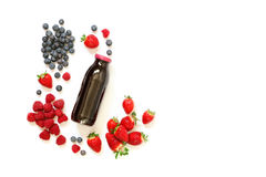 Bottle of strawberries, raspberries, blueberries juice isolated on white. Glass bottle of berries juice from strawberries, raspberries, blueberries and Stock Photography
