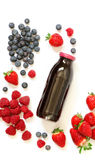 Bottle of strawberries, raspberries, blueberries juice isolated on white. Glass bottle of berries juice from strawberries, raspberries, blueberries and Stock Photos
