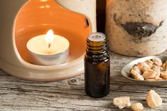 A bottle of styrax benzoin essential oil with an aroma lamp. A bottle of styrax benzoin essential oil with benzoin resin and an aroma lamp royalty free stock images
