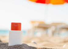 Bottle of sun block creme in shadow on beach Royalty Free Stock Photo
