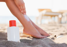 Bottle of sun block and female applying creme Stock Photography