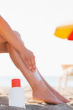 Bottle of sun block and female applying creme Royalty Free Stock Photos