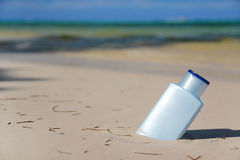 Bottle with Sunblock lotion on tropical beach Royalty Free Stock Image