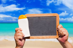 Bottle Sunscreen and blank slate blackboard Stock Image
