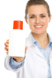 Bottle of sunscreen in hands of cosmetologist Stock Images