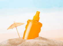 Bottle of sunscreen in the sand against  sea. Stock Images