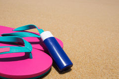 Bottle of sunscreen on the sandy beach Royalty Free Stock Photo