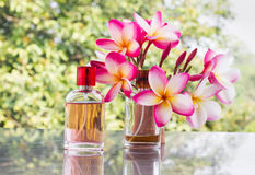 Bottle of sweet pink fragrant perfume with pink flower plumeria Royalty Free Stock Image