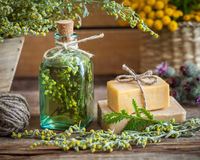 Bottle of tarragon tincture, healthy herbs and bars of soap Stock Images
