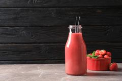 Bottle with tasty strawberry smoothie. On table royalty free stock photography